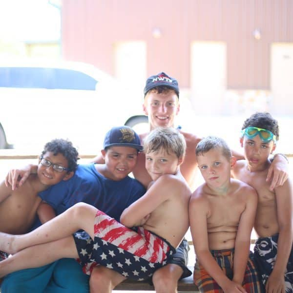 Summer camp boys spending time with their counselor at the Christian youth summer camp Shepherd's Fold Ranch.