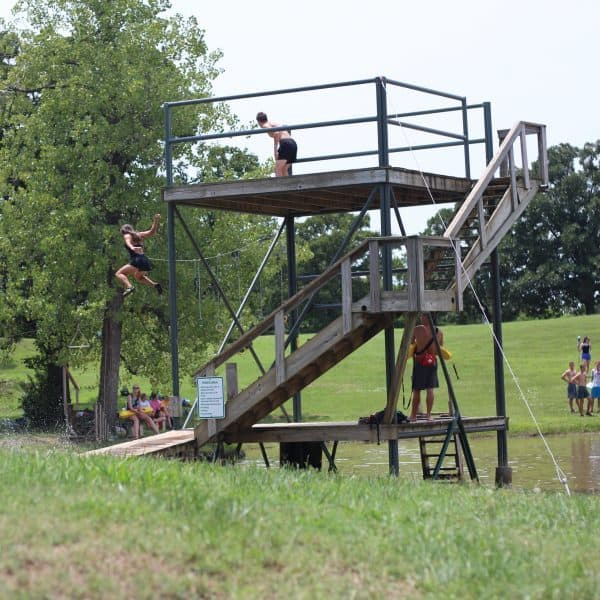 Treehouse vilalge kids having fun in the summer jumping into the pond at summer camp, Shepherd's Fold Ranch.