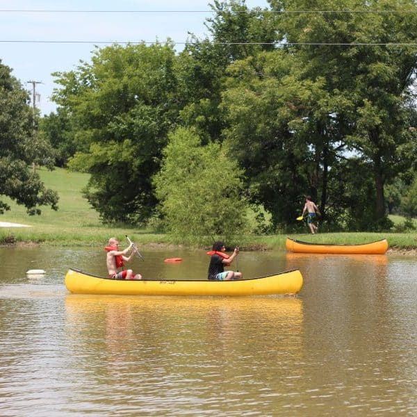 Kids canoeing in pond at Christian youth camp Shepherd's Fold Ranch